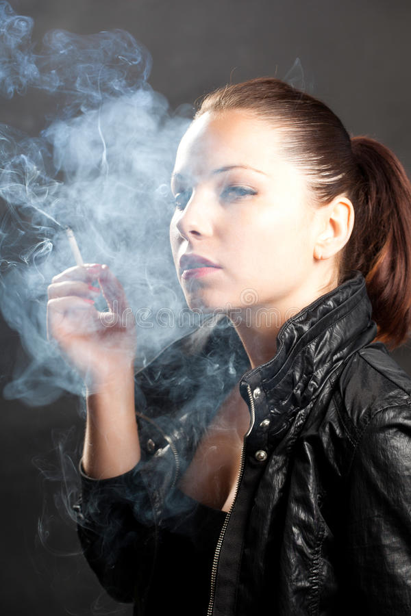 Don't Play With Me!. Woman Smoking In The Studio, Looking At The Camera royalty free stock image