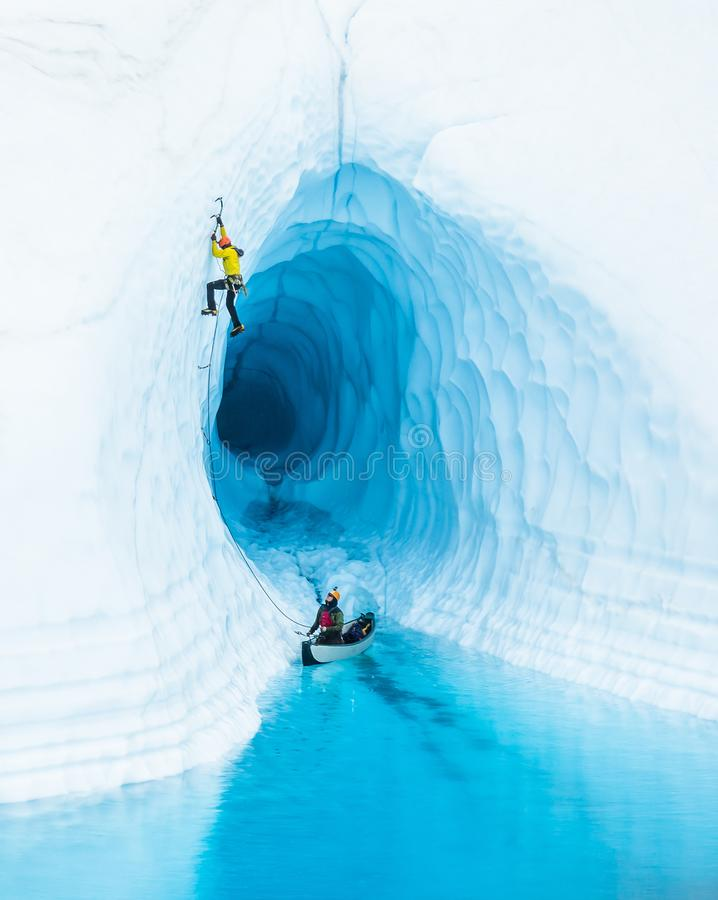 Don`t Pop the Boat! - Ice climber leading up from inflatable canoe in a glacier lake on the Matanuska Glacier in Alaska royalty free stock images