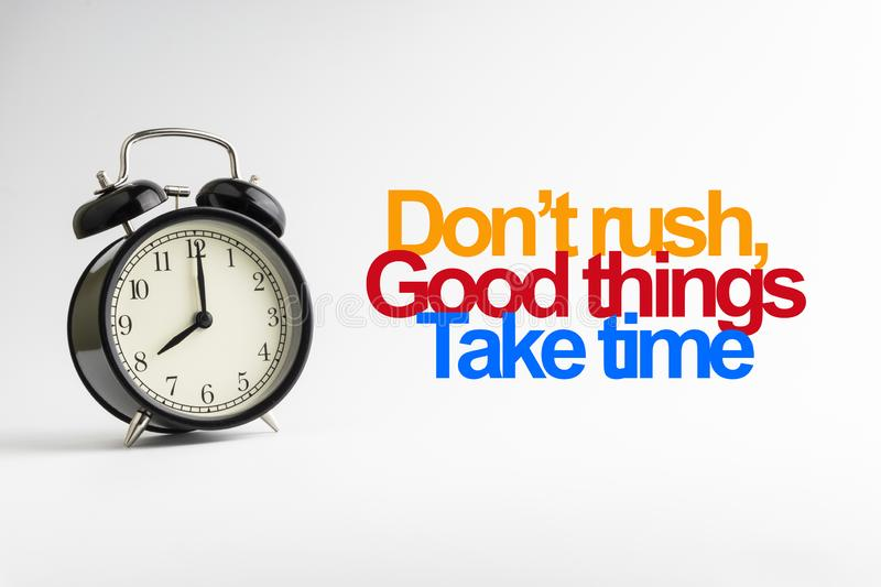 DON`T RUSH GOOD THINGS TAKE TIME inscription written and alarm clock on white background royalty free stock images