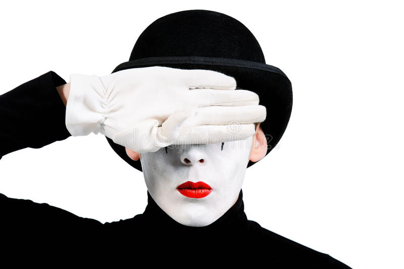 Don't see. Close-up portrait of a male mime artist closing his eyes with his hand. Isolated over white stock image
