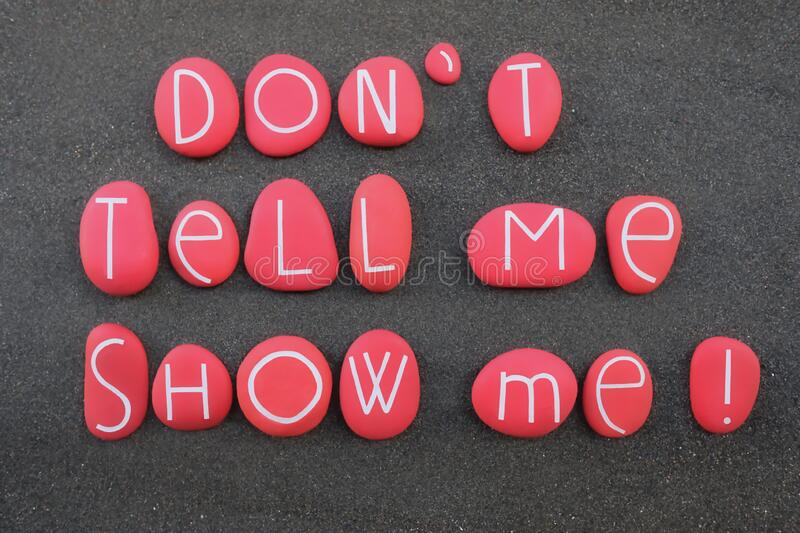 Don`t tell me, show me. Motivational phrase composed with red colored and carved stone letters over black volcanic sand royalty free stock image