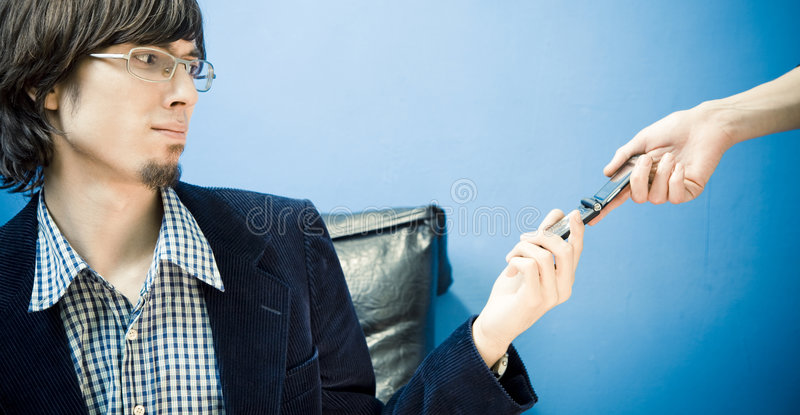 Don't Wanna Take That. Young man taking a cell phone from an anonymous person, with an expression indicating he does not want to take the call. Horizontal format royalty free stock image