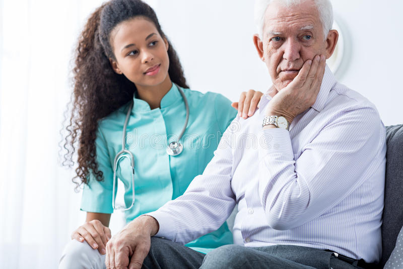 Don't worry, i'm here to help you. Afroamerican carer sitting next to worried elderly man stock photography