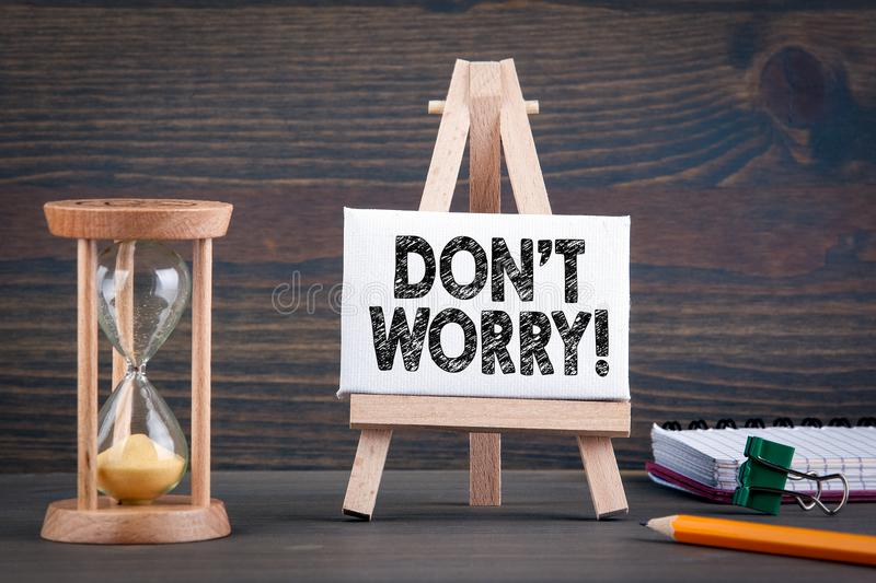 Don`t Worry. Sandglass, hourglass or egg timer on wooden table stock photo