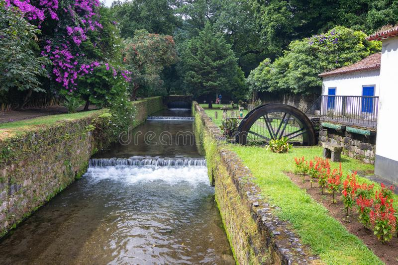 Dona Beatriz do Canto park in Furnas town, Sao Miguel island, Azores. Scenic view of a river, water mill and blooming flowers in summer stock photography