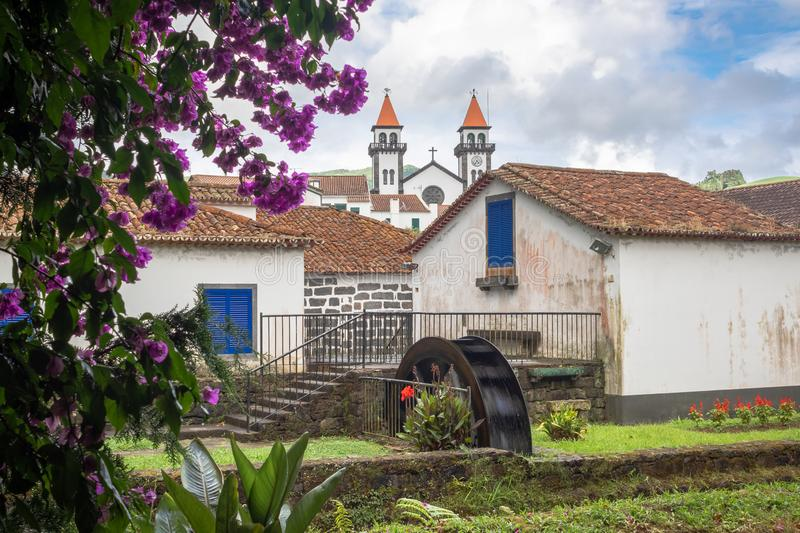 Dona Beatriz do Canto park in Furnas town, Sao Miguel island, Azores. Scenic view of the park with a water mill, blooming flowers and church steeples in summer stock photos
