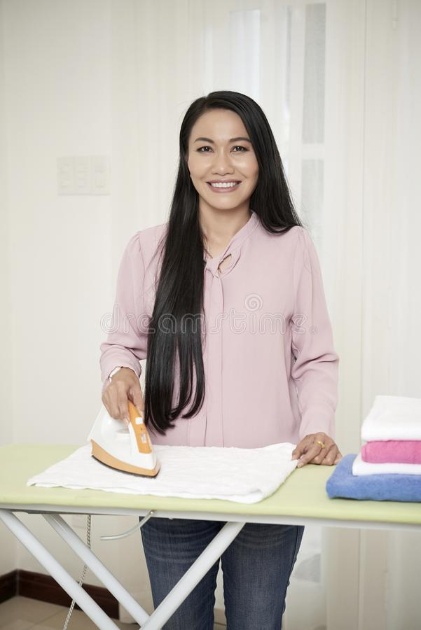 Dona de casa adulta de sorriso com ferro em casa imagem de stock royalty free