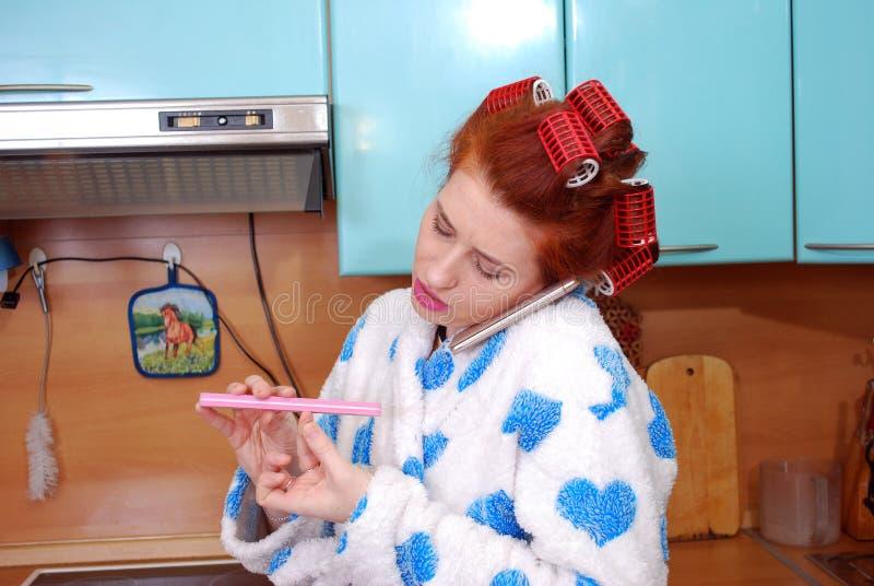 A dona de casa atrativa nova na cozinha em encrespadores de cabelo fala pelo telefone e faz o tratamento de mãos foto de stock