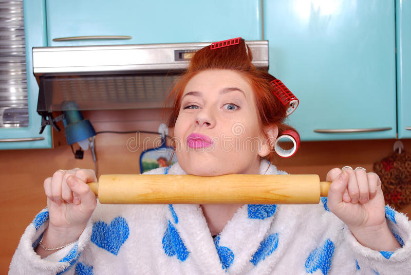 A dona de casa atrativa nova na cozinha sobre encrespadores de cabelo e mantém um pino do rolo em um vestido de molho imagens de stock royalty free
