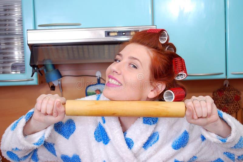 A dona de casa atrativa nova na cozinha sobre encrespadores de cabelo e mantém um pino do rolo em um vestido de molho foto de stock