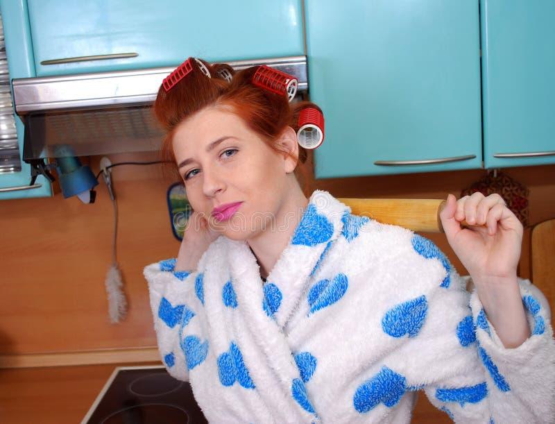 A dona de casa atrativa nova na cozinha sobre encrespadores de cabelo guarda um pino do rolo atrás da parte traseira fotos de stock royalty free