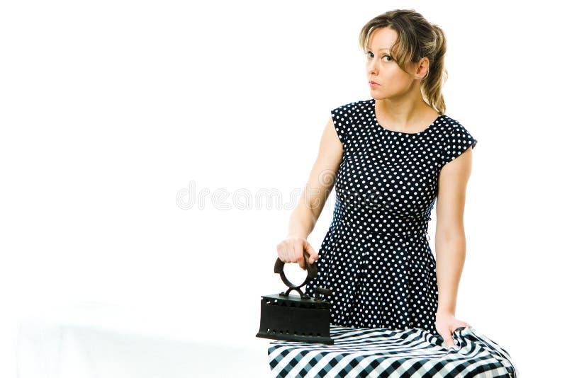 Dona de casa atrativa que passa o vestido quadriculado usando a ferramenta passando do metal de carvão do vintage fotografia de stock