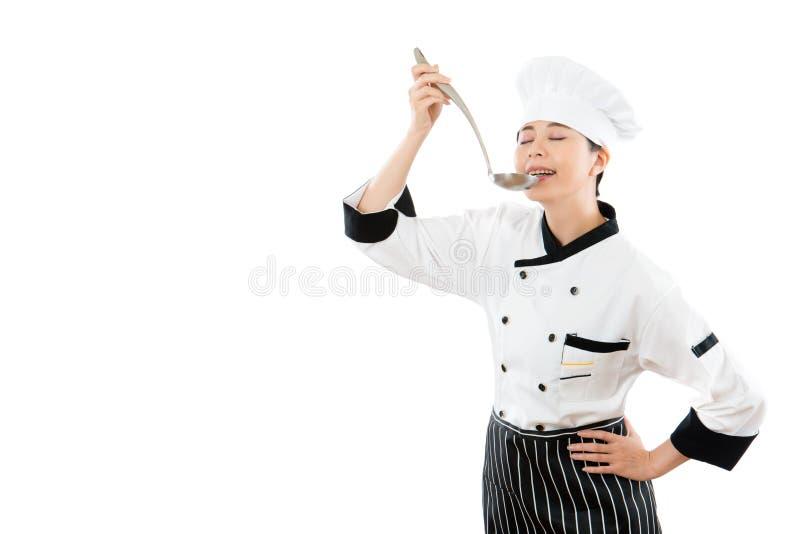 Dona de casa bonita que veste uma roupa do cozinheiro chefe fotografia de stock