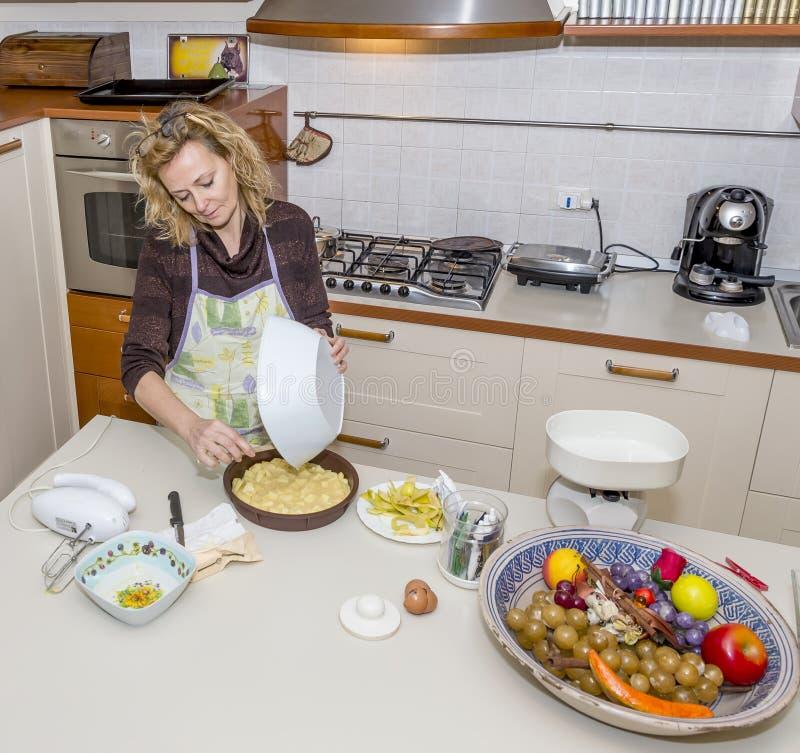 A dona de casa bonito prepara um bolo em uma cozinha desarrumado fotografia de stock
