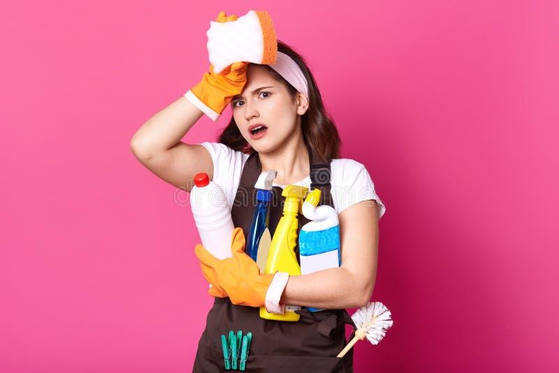 Dona de casa cansado nova no avental marrom e camisa ocasional branca de t, com deretgents de limpeza, no fundo cor-de-rosa A fêm imagem de stock