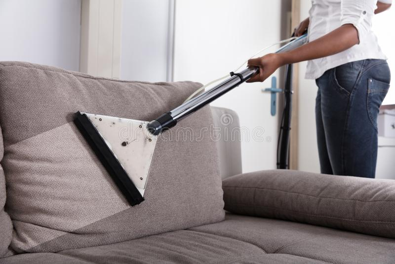Dona de casa Cleaning Sofa With Vacuum Cleaner imagem de stock