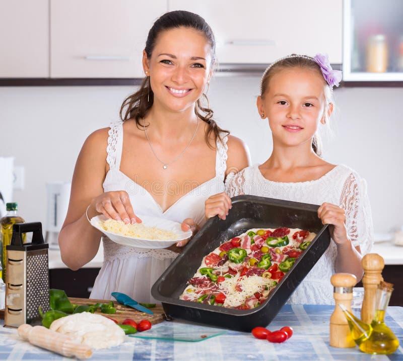 Dona de casa com a menina que cozinha a pizza fotos de stock royalty free