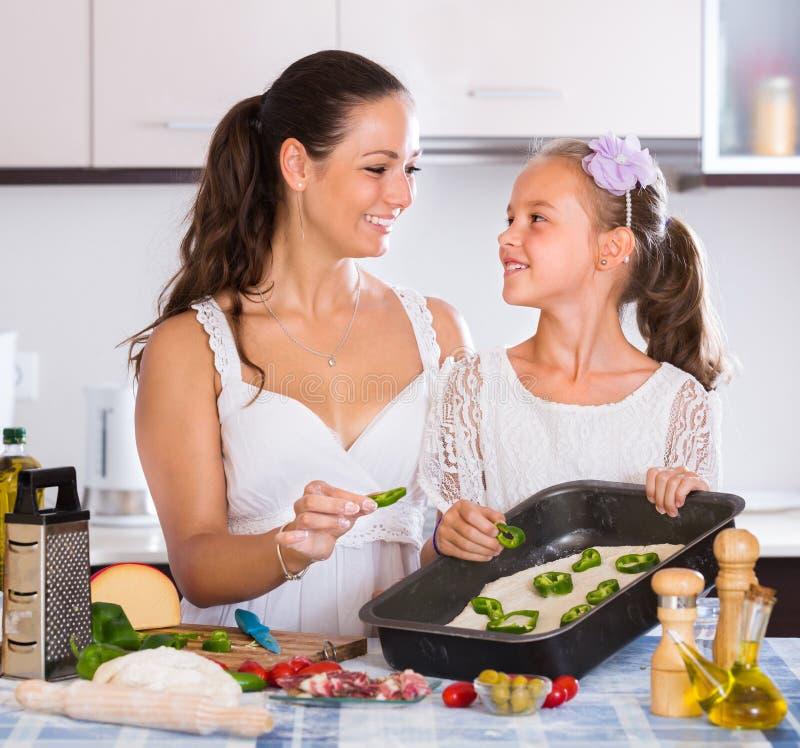 Dona de casa com a menina que cozinha a pizza fotos de stock