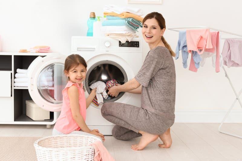 Dona de casa com sua filha pequena que faz a lavanderia em casa fotografia de stock royalty free