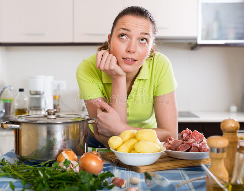 Dona de casa confusa na cozinha foto de stock royalty free