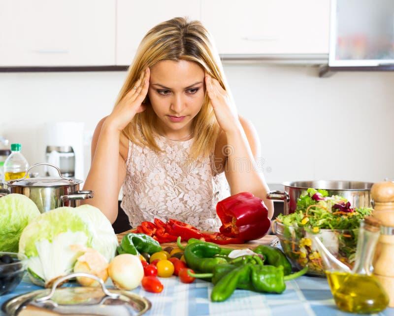 Dona de casa confusa na cozinha imagem de stock