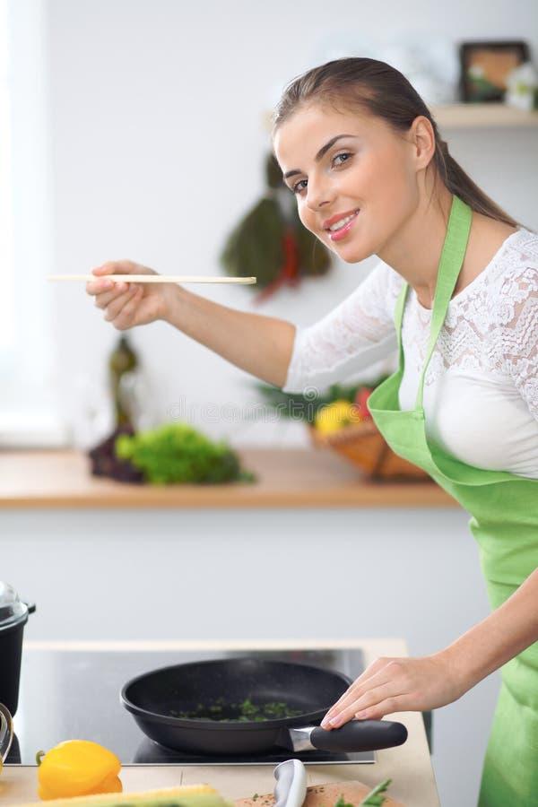 Dona de casa da jovem mulher que cozinha na cozinha Conceito da refeição fresca e saudável em casa imagem de stock royalty free