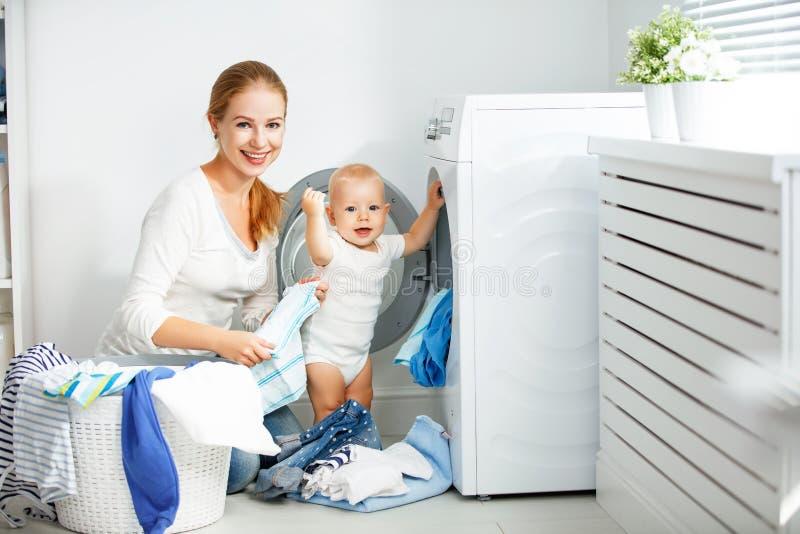 A dona de casa da mãe com bebê contratou na roupa da dobra da lavanderia em imagem de stock royalty free