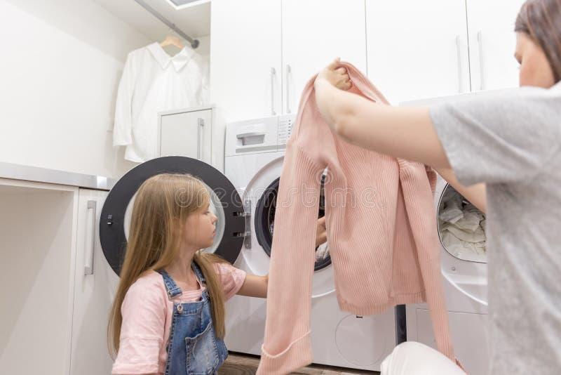 Dona de casa da mãe da família e filha felizes da criança na lavanderia com máquina de lavar e roupa imagens de stock