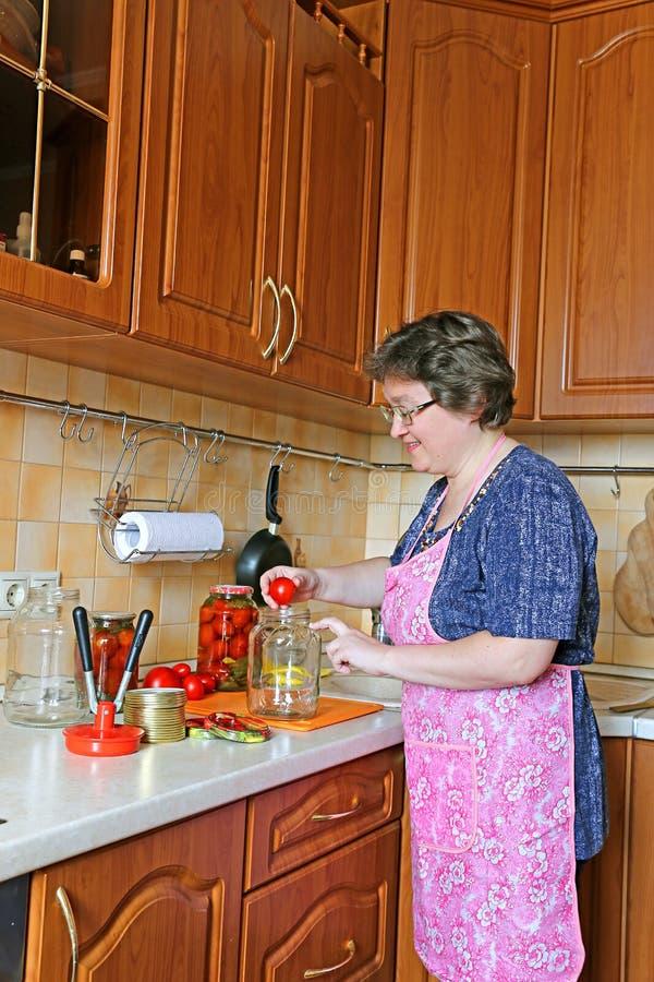 Dona de casa da mulher contratada em vegetais de colocação em latas imagens de stock royalty free