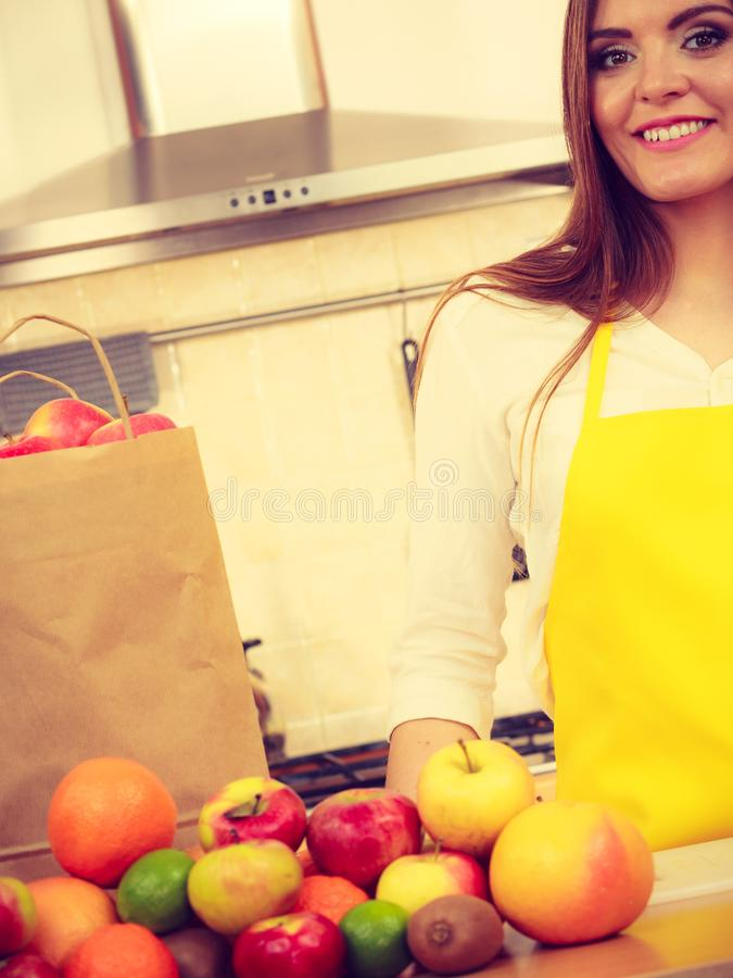 Dona de casa da mulher na cozinha com muitos frutos imagens de stock