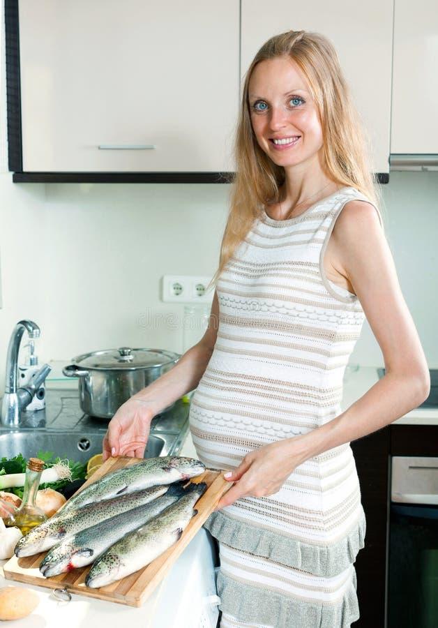 Dona de casa de sorriso que cozinha a truta fotografia de stock