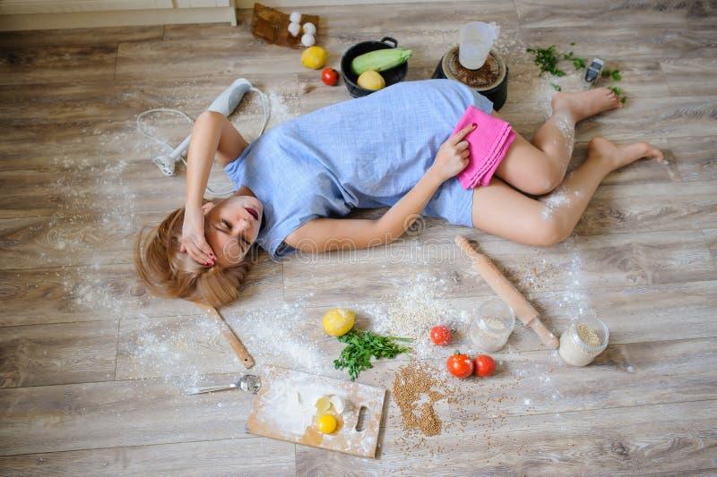 dona de casa desesperada que encontra-se no assoalho em sua cozinha fotos de stock royalty free