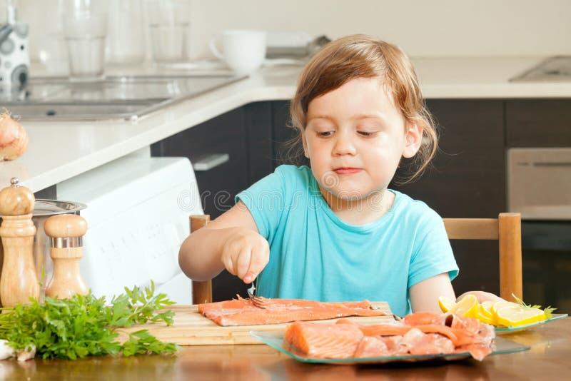Dona de casa do bebê que cozinha salmões fotos de stock