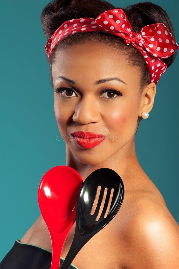 Dona de casa do estilo de Pinup com utensílios da cozinha foto de stock
