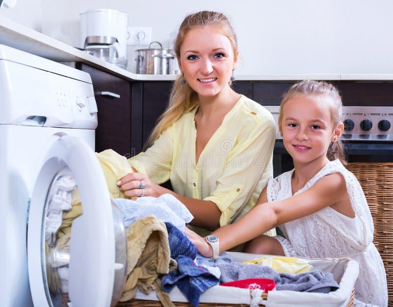 Dona de casa e menina que fazem a lavanderia fotografia de stock