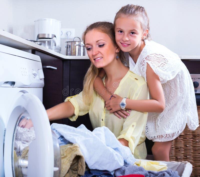 Dona de casa e menina que fazem a lavanderia imagem de stock royalty free