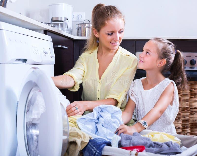 Dona de casa e menina que fazem a lavanderia imagens de stock