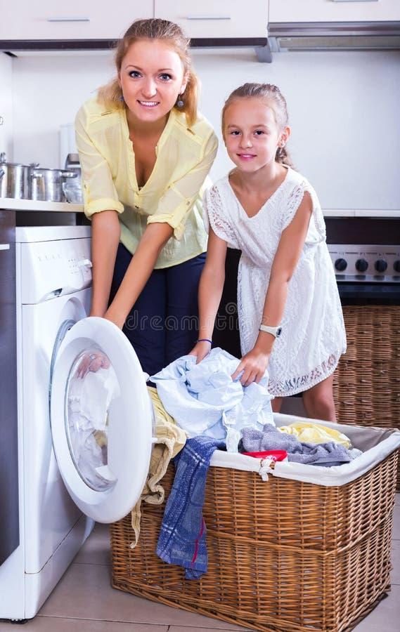 Dona de casa e menina que fazem a lavanderia fotos de stock