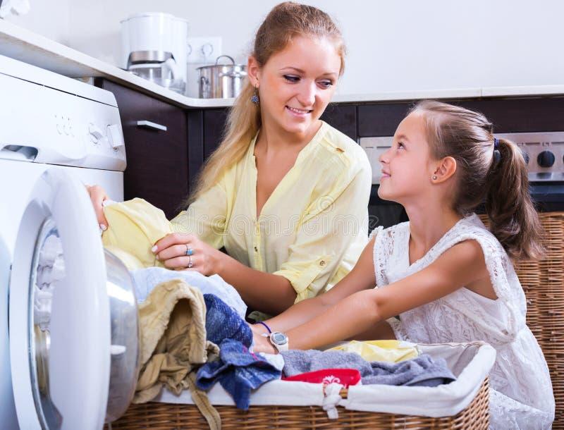 Dona de casa e menina que fazem a lavanderia fotografia de stock royalty free