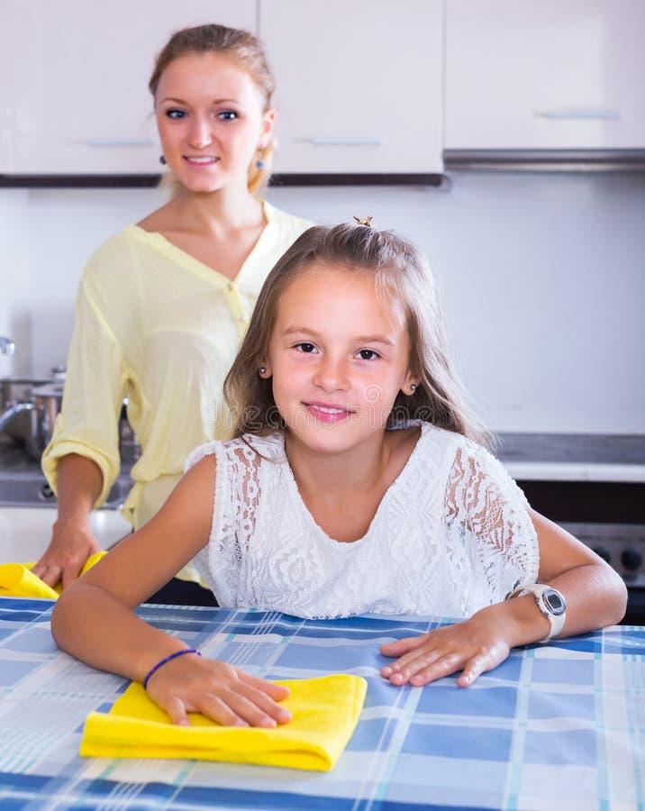 Dona de casa e menina que limpam junto imagem de stock