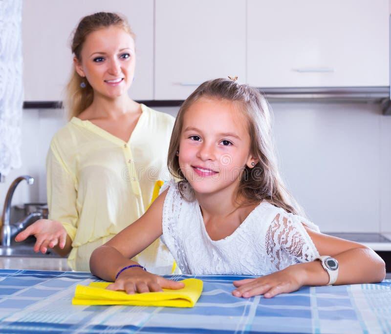 Dona de casa e menina que limpam junto imagem de stock royalty free