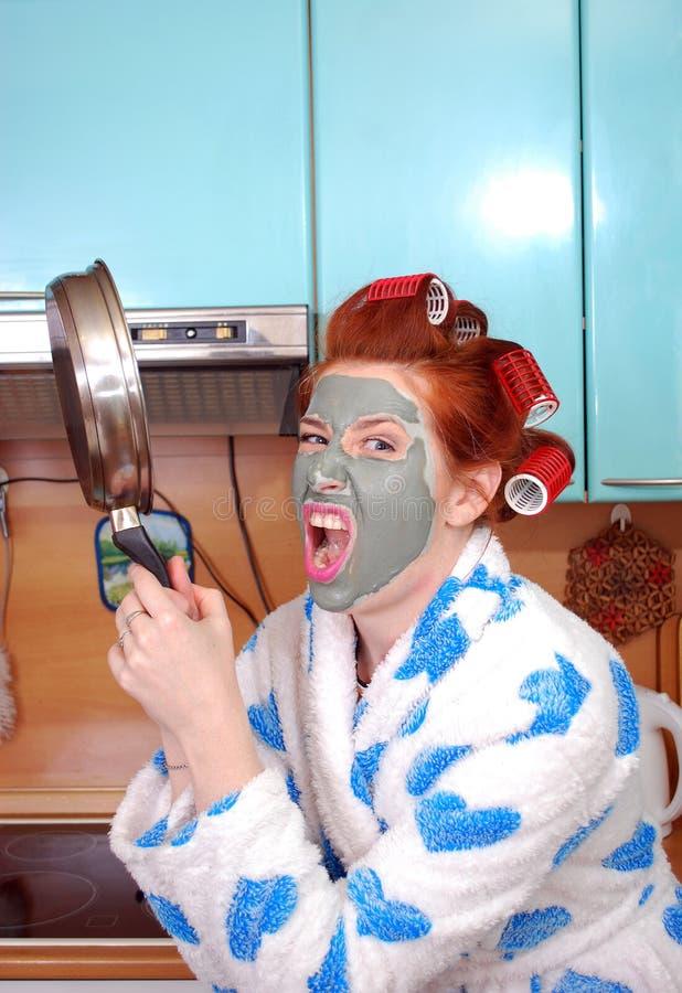 A dona de casa emocional nova com cabelo vermelho em encrespadores de cabelo e com uma máscara da argila em uma cara na raiva ame imagem de stock