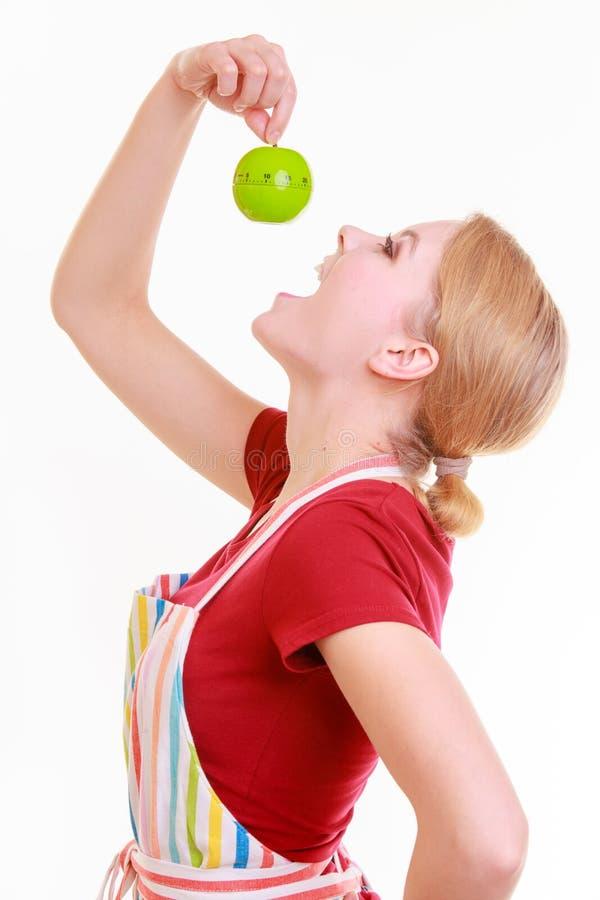 Dona de casa engraçada no avental da cozinha que tenta comer o temporizador da maçã isolado imagens de stock royalty free