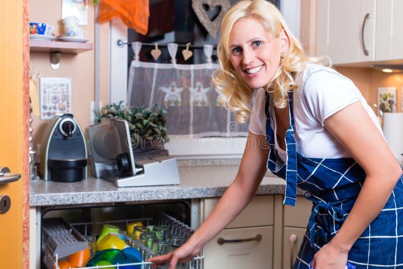 A dona de casa está fazendo os pratos com máquina de lavar louça imagens de stock royalty free
