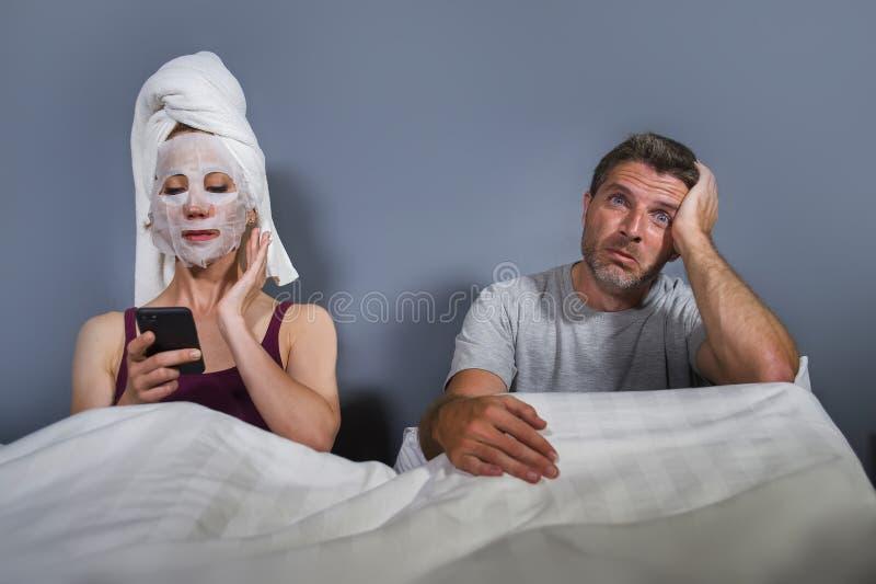 Dona de casa excêntrica e estranha com máscara e toalha faciais da composição usando o telefone celular na cama e marido na expre fotografia de stock royalty free