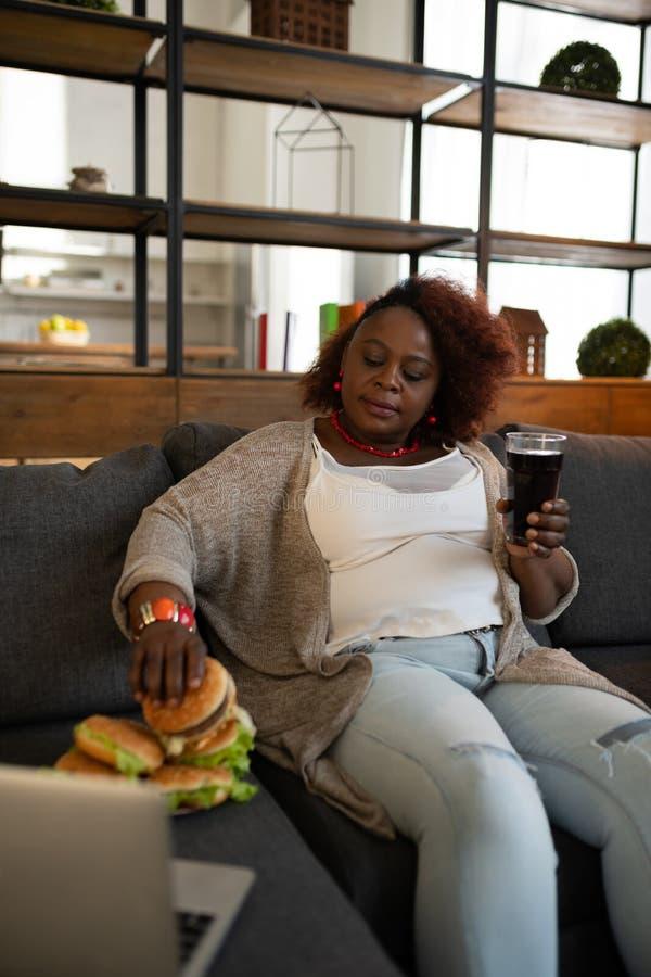 Dona de casa excesso de peso relaxado que vai comer o Hamburger imagens de stock