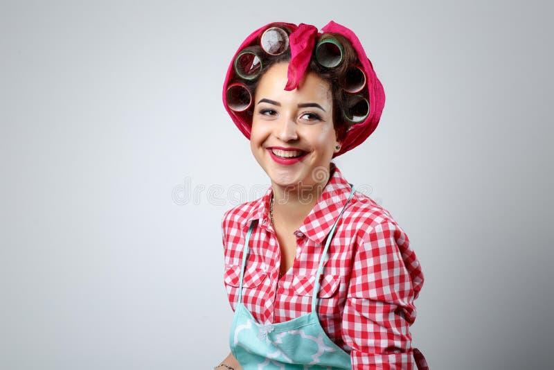 Dona de casa feliz da menina em um fundo cinzento fotografia de stock royalty free