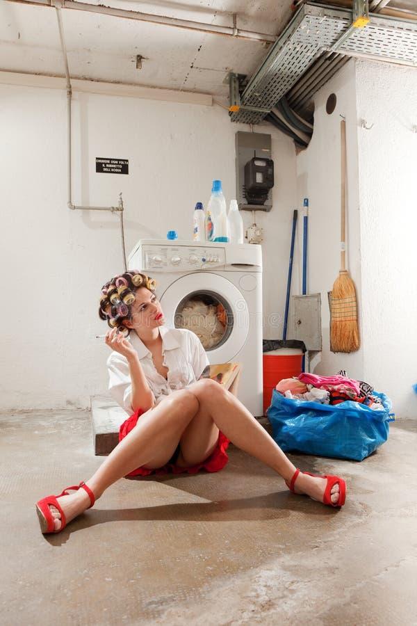 Dona de casa furada na lavanderia imagens de stock