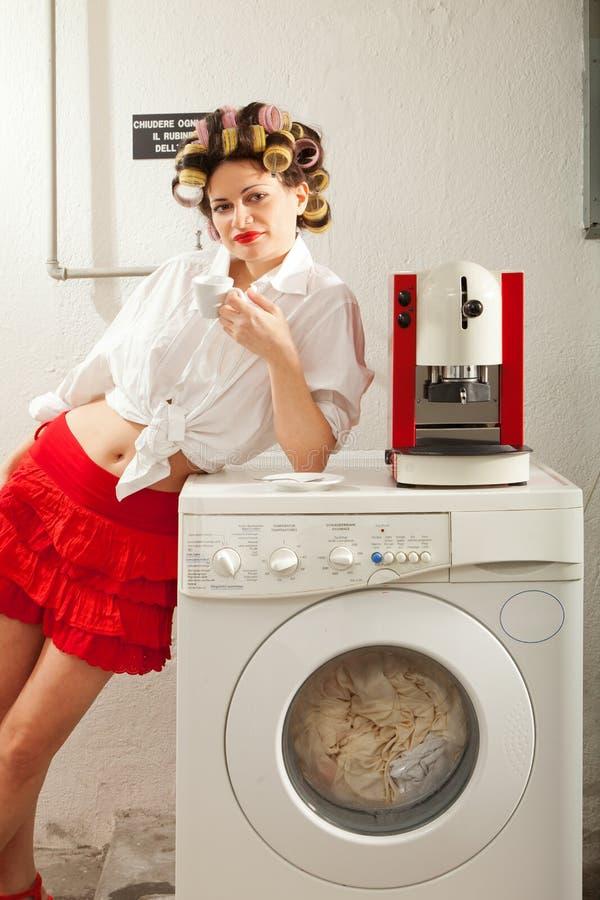 Dona de casa furada na lavanderia foto de stock