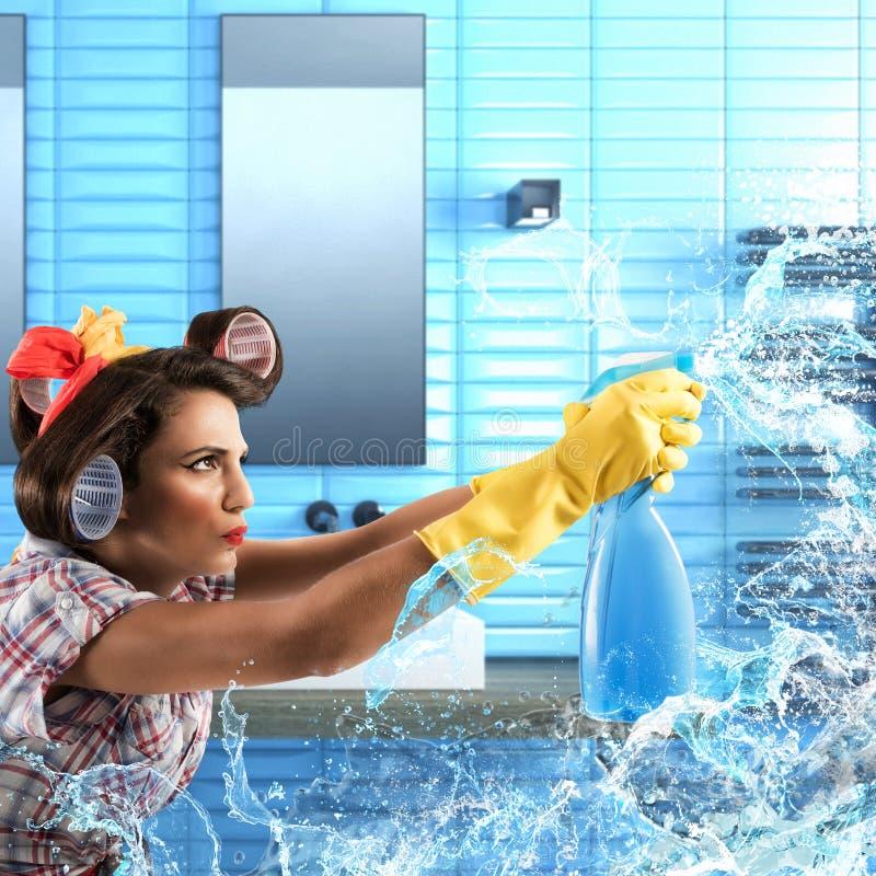 A dona de casa limpa com o pulverizador do sabão fotografia de stock royalty free